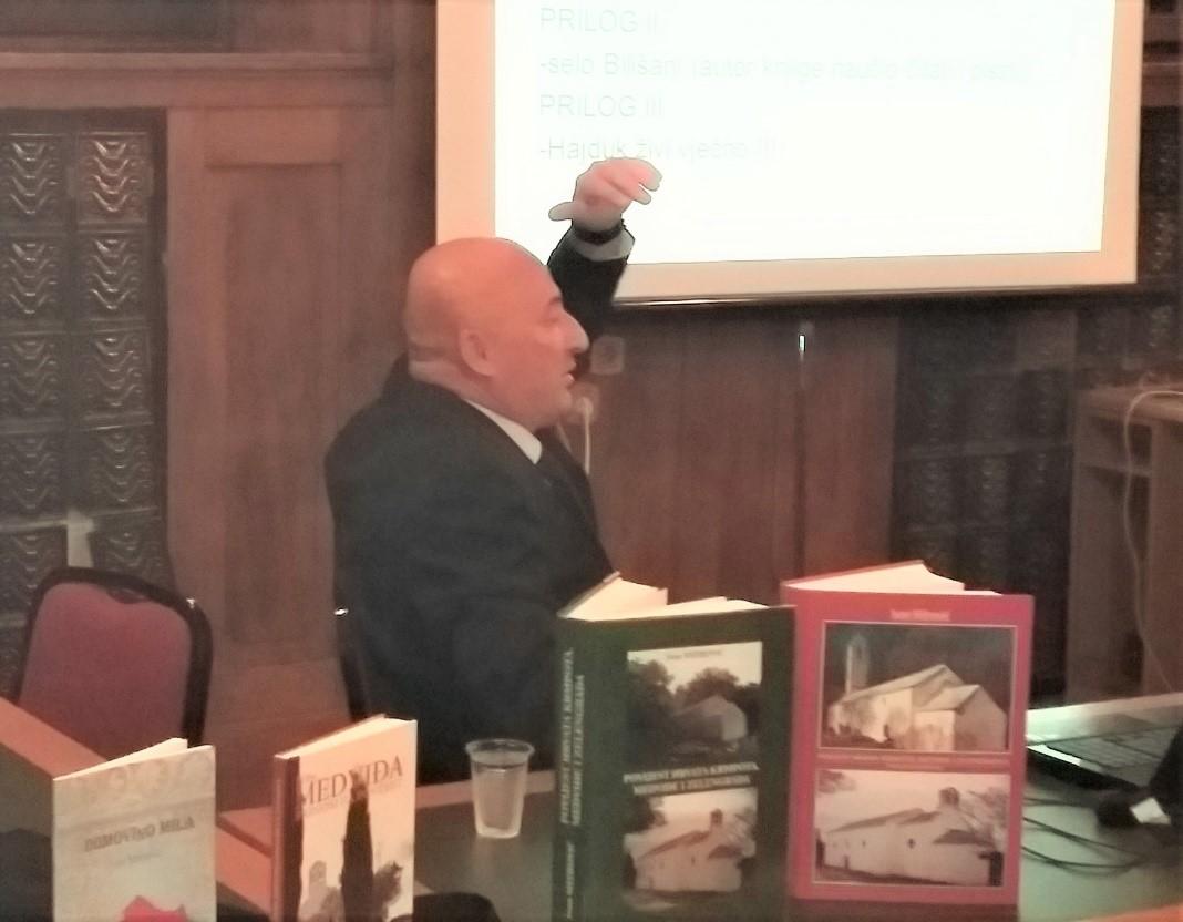 G. Ivan Mitrović na predavanju o svom istraživanju povijesti Hrvata Krmpota, Medviđe i Zelegrada; u prvom planu su njegove knjige na tu temu